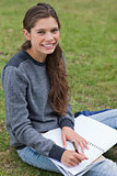 Smiling young woman writing on her notebook while looking at the