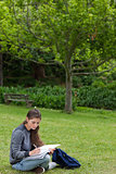 Young serious girl doing her homework while sitting down in a pa