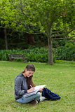 Smiling young girl writing on her notebook while sitting on the