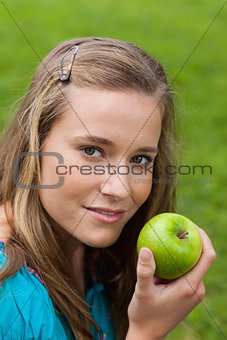Attractive young girl holding a delicious green apple while stan