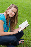 Young relaxed girl reading a book while sitting in the countrysi