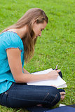 Serious young girl writing on her notebook while sitting on the