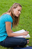 Attractive young girl sitting down in a park while doing her hom