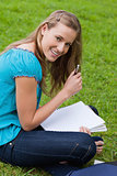Young smiling student holding her pen while looking at the camer