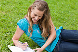 Young smiling girl lying on the grass while writing on a noteboo