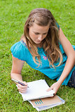 Young serious girl lying on the grass in a park while writing on