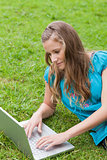 Young serious girl lying on the grass while using her laptop