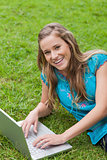 Smiling teenage girl lying on the side while using her laptop
