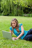 Young relaxed girl lying on the side while working on her laptop