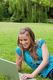 Young smiling girl lying down in a park while using her laptop