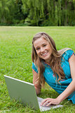 Young girl looking at the camera while using her laptop and smil