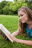 Serious young woman reading a book while lying on the grass