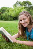 Smiling teenage girl holding a book in a parkland while looking