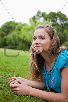 Thoughtful young girl looking away while lying on the grass