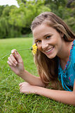 Young smiling girl smelling a yellow flower while lying on the g