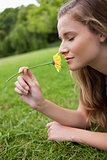 Young calm woman closing her eyes while smelling a yellow flower