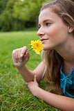 Young girl lying on the grass while smelling a flower