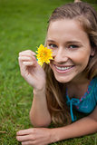 Smiling young woman showing a yellow flower while lying on the g