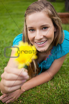 Smiling young woman holding a yellow flower while looking at the