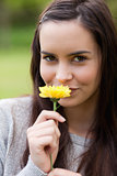 Young woman looking at the camera while smelling a yellow flower