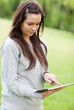 Serious young woman standing up while using her tablet computer