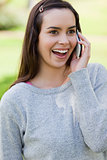 Surprised young woman talking on the phone while standing in a p