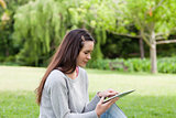Young relaxed woman sitting in a park while using her tablet pc