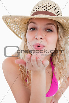 Young blonde woman sending an air kiss in front of the camera