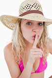 Young woman telling to be quiet with her finger on her mouth