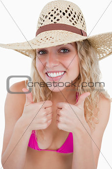 Smiling blonde teenager showing her two thumbs up