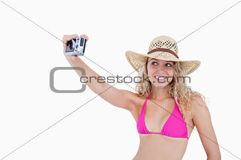 Smiling teenager photographing herself with a digital camera