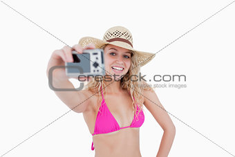 Beautiful teenage girl holding a camera while photographing hers
