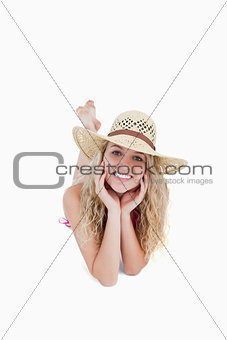 Smiling teenager wearing a hat while lying down