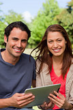 Man and a woman look ahead while holding a tablet