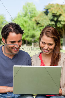 Two friends smiling as they watch something on a tablet