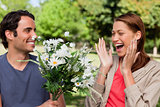 Woman laughing excitedly as she is presented with flowers by her