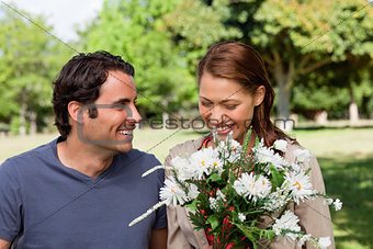 Woman happily looking into a bunch flowers as she is being watch