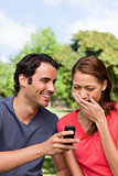 Woman aughing at something being shown to her on her friend&#39;s ph