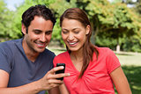 Two friends smiling as they are looking at something on a mobile