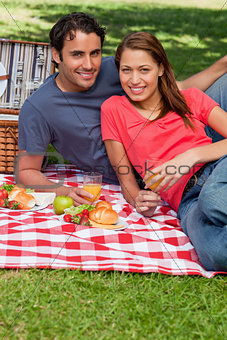 Two friends holding glasses while looking ahead during a picnic