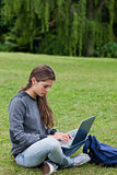 Serious young woman typing on her laptop while sitting cross-leg