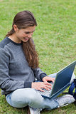 Smiling student typing on her laptop while sitting down on the g