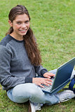 Smiling young girl sitting down in a park while using her laptop