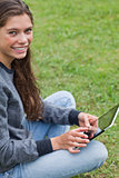 Young smiling girl sitting down with her tablet pc while looking
