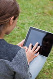 Rear view of a young girl using her tablet pc