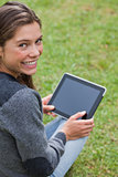 Young girl using her tablet pc while sitting down and showing a