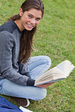 Young smiling woman sitting cross-legged in a park while holding