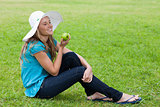 Young smiling girl sitting on the grass with a hat while holding