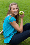 Smiling young woman holding a green apple while sitting in a par