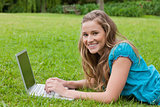 Smiling teenager using her laptop while lying down in a park